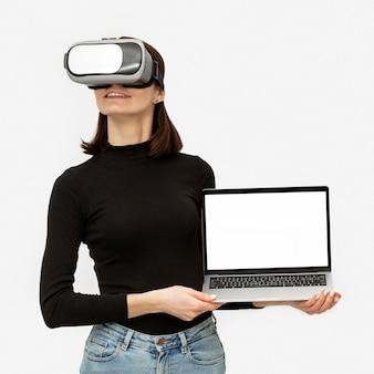 Donna con la cuffia avricolare di realtà virtuale che tiene il computer portatile