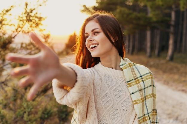 Una donna con una calda coperta sulla spalla allunga la mano in avanti e tramonta all'aria fresca della natura. foto di alta qualità