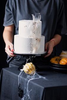 Donna con torta glassata bianca, decorazione di halloween sul tavolo nero, messa a fuoco selettiva immagine