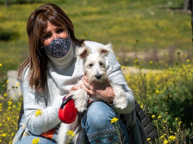 Donna con cane schnauzer bianco nel campo di fiori gialli yellow