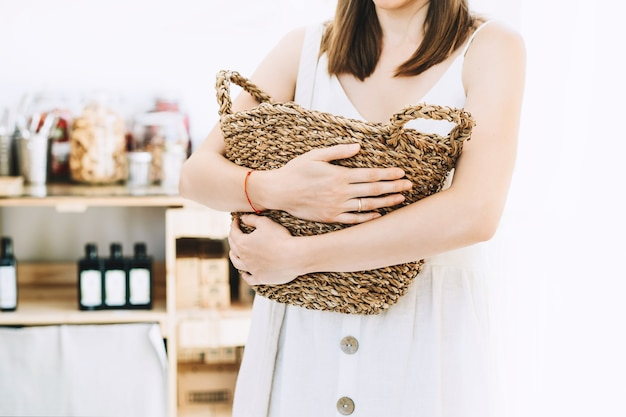 Donna con cesto di vimini acquisto in plastica free drogheria zero rifiuti shop