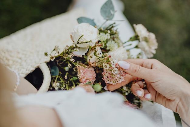 Donna con una borsa intrecciata piena di fiori
