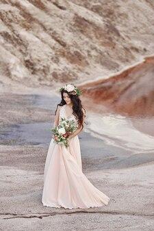 Donna con una corona di fiori sulla testa e un mazzo di bellissimi fiori in mano cammina su uno sfondo di montagne. il lungo abito estivo leggero fluttua nel vento