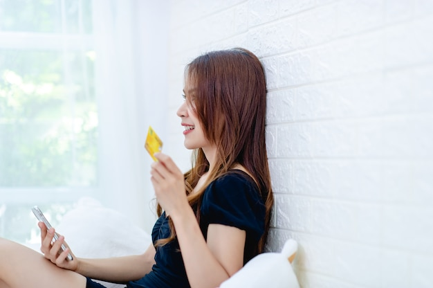 Donna con una carta di credito gialla in mano sorridendo felicemente sul letto in camera da letto idea di business