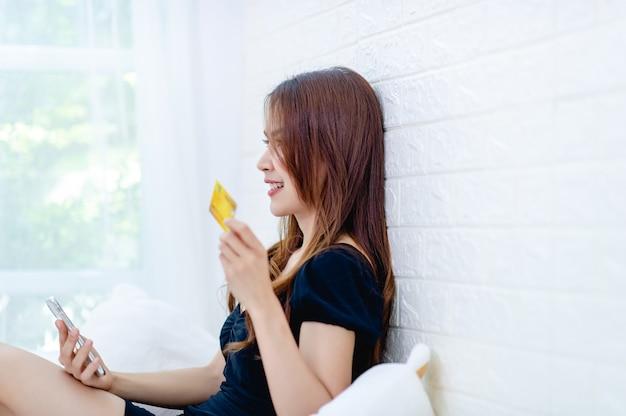 Donna con una carta di credito gialla in mano