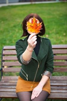 Una donna con una foglia d'acero gialla caduta si copre il viso. ritratto autunnale senza volto su una panchina del parco. atmosfera autunnale