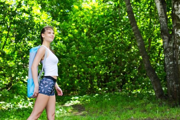 Donna con materassino yoga nel parco. concetto di stile di vita sano, yoga e sport