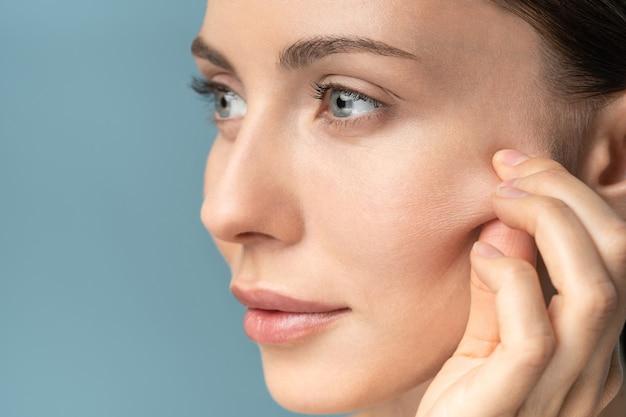 La donna senza trucco che tocca le guance dopo la buccia di acido glicolico, ha segni di invecchiamento della pelle sul viso