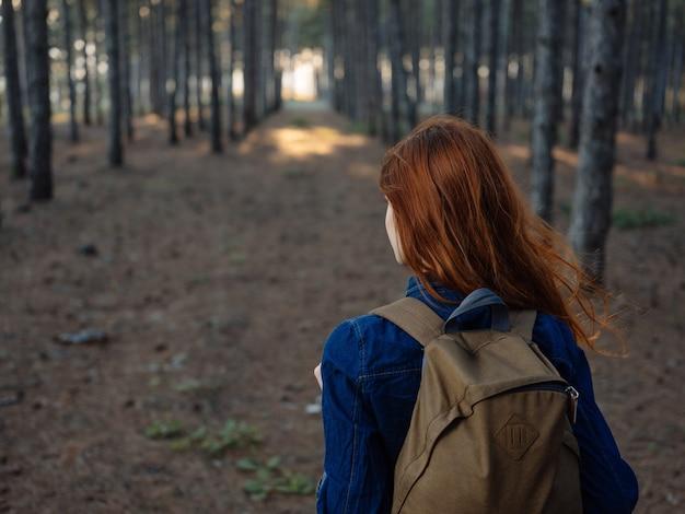 Donna nel bosco all'aperto viaggio a piedi
