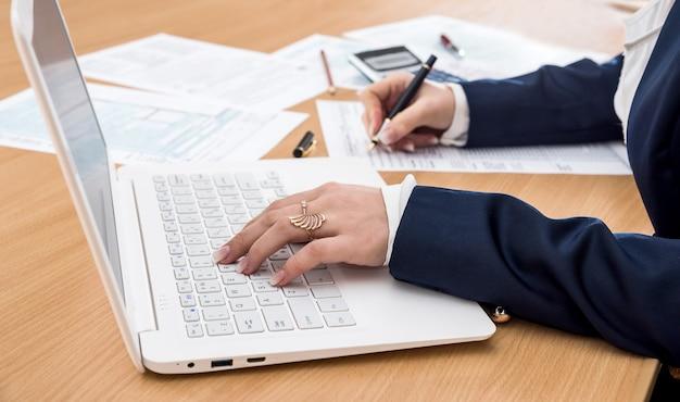 La donna lavora al laptop e compila il modulo fiscale