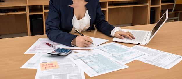 La donna lavora al computer portatile e riempiendo il modulo fiscale