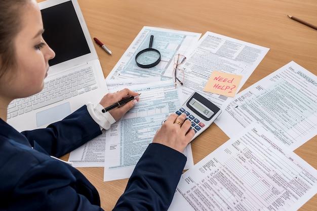 La donna lavora in ufficio - calcolatore del reddito del modulo di dichiarazione dei redditi