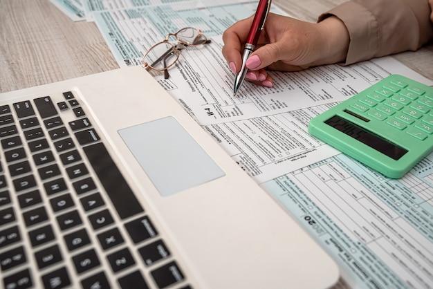 La donna lavora con il modulo fiscale usa 1040 e il computer portatile della calcolatrice in ufficio. concetto di contabilità