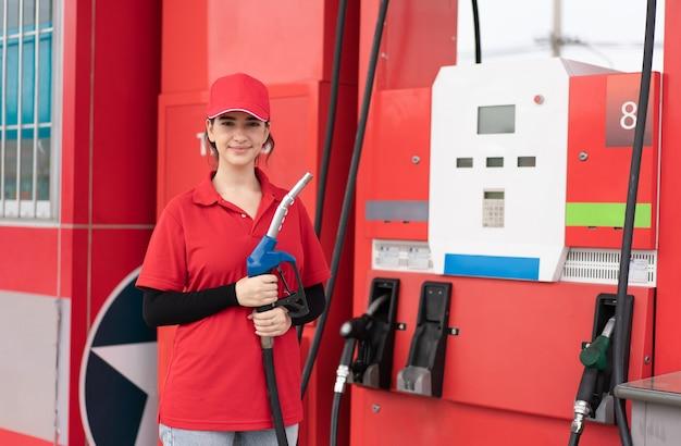 Lavoratrice in uniforme rossa che tiene l'ugello della pompa del carburante pronto per il servizio alla stazione di servizio