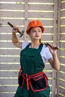 Lavoratrice con strumenti. giovane ragazza in tuta e casco in posa sul sito in costruzione