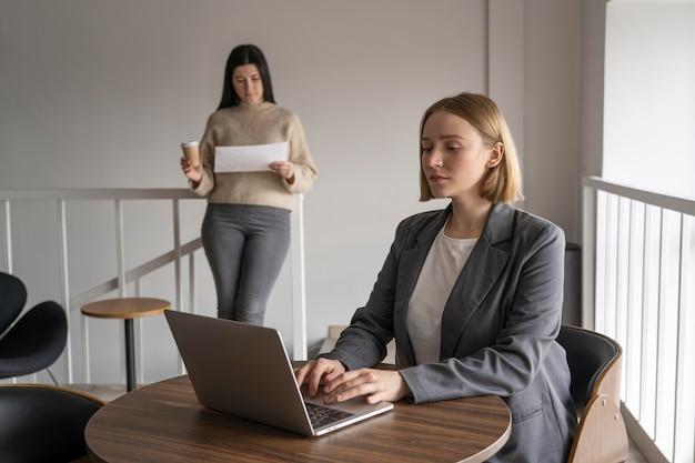 Donna che lavora da sola mentre si allontana sociale dagli altri colleghi