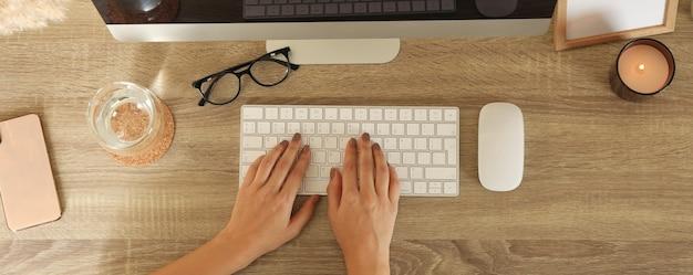 Donna che lavora su computer desktop su un tavolo di legno