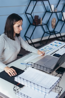 Donna che lavora alla sua scrivania con documenti e laptop.