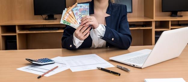 Donna che lavora a casa buget con laptop e conto euro bill