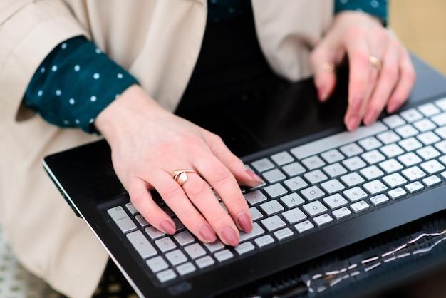 Donna che lavora in ufficio a casa e all'aperto, mano sulla tastiera da vicino, laptop