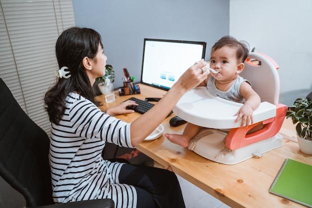Donna che lavora a casa e prendersi cura del suo bambino