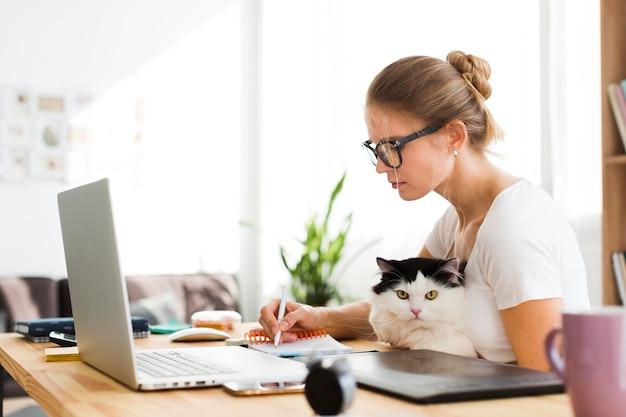 Donna che lavora al computer portatile a casa mentre si tiene gatto