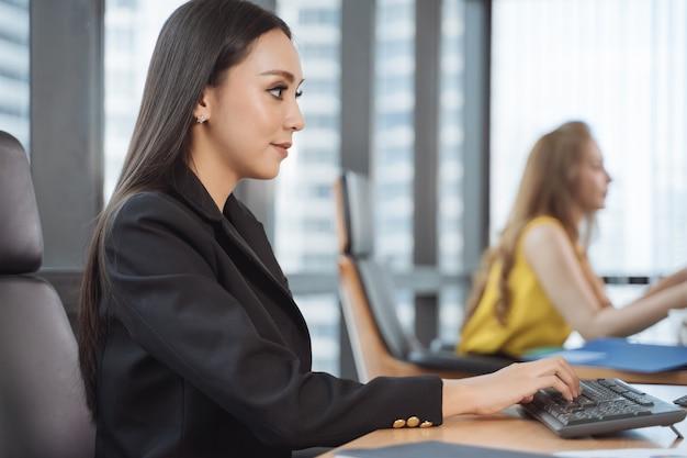 Donna che lavora al computer portatile all'ufficio