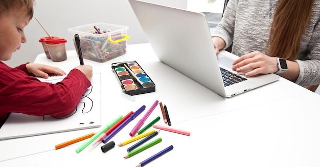 Donna che lavora al computer portatile mentre suo figlio sta dipingendo