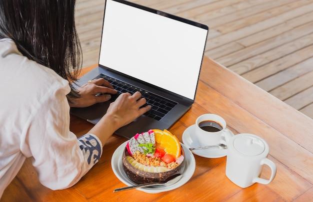 Donna che lavora al computer portatile con ciotola di colazione frullata e caffè sul tavolo.