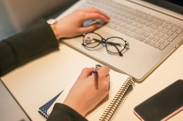 Donna che lavora al computer portatile e scrivere sul taccuino di carta. chiuda in su delle mani della donna che prendono appunti.