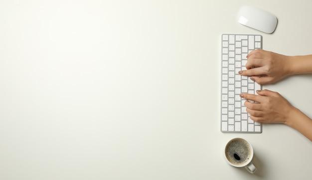 Donna che lavora sulla tastiera moderna su sfondo bianco