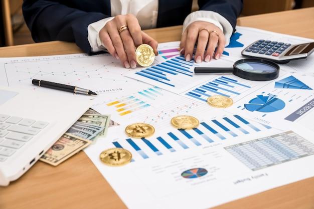 Donna che lavora al laptop e al dollaro del grafico di affari di bitcoin dell'ufficio