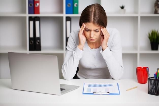 Donna che lavora alla scrivania in ufficio davanti al computer portatile che soffre di mal di testa cronici quotidiani.