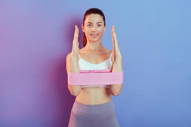 Donna che allena la mano con fascia di resistenza, signora che si mette in forma, indossa top e leggins, allena i muscoli, posa contro il muro colorato.