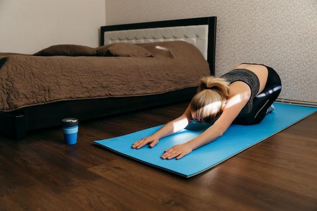 Donna che lavora a casa su una stuoia di yoga