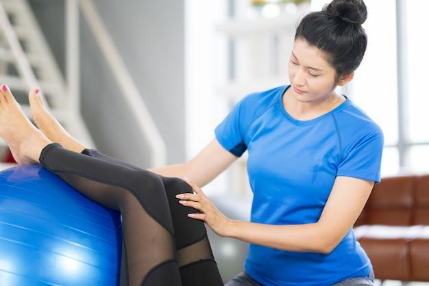 Donna che risolve con palla fitness di sportivi che praticano yoga. fare stretching con la palla fitness a casa