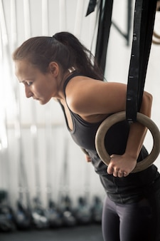 Donna che risolve con gli anelli relativi alla ginnastica alla palestra adatta dell'incrocio