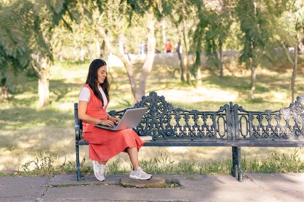 Donna che lavora nel parco con il suo laptop seduta su una panchina con alberi