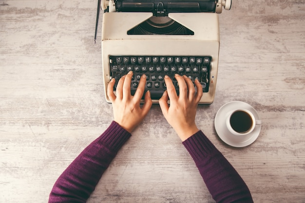 Donna che lavora nel caffè della mano della macchina da scrivere
