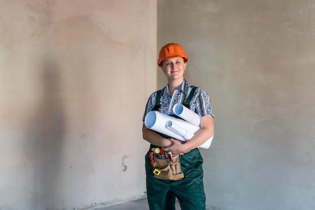 Donna in uniforme da lavoro con cintura degli attrezzi e progetti