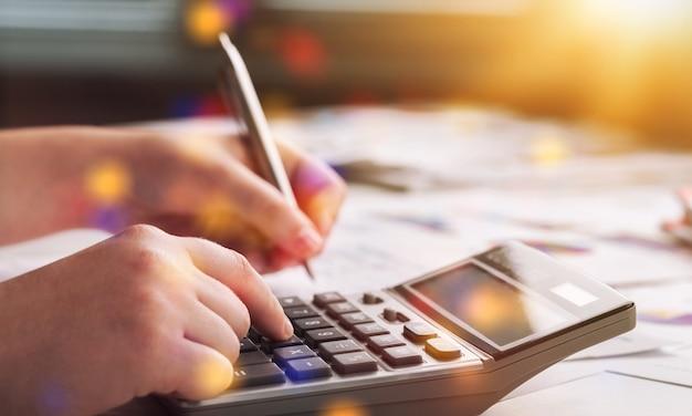 Donna che lavora con calcolatrice, documento aziendale e computer portatile notebook