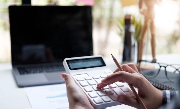 Donna che lavora con calcolatrice, documento aziendale e notebook del computer portatile