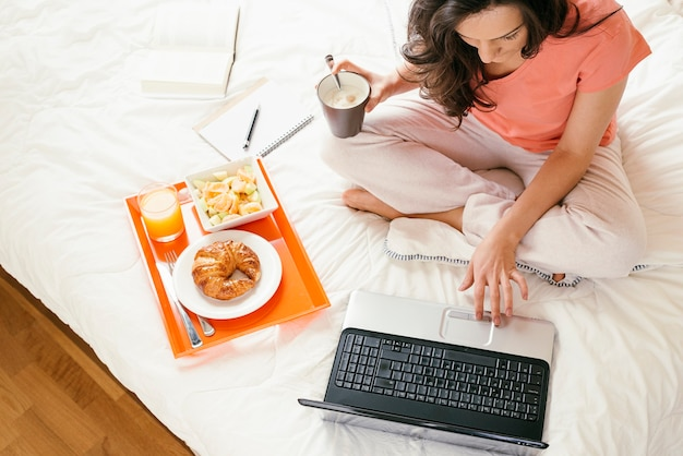 Donna che lavora con il suo computer portatile e fa colazione. è nella sua camera da letto.