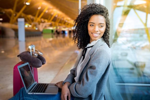 Donna che lavora con il computer portatile all'aeroporto che aspetta alla finestra
