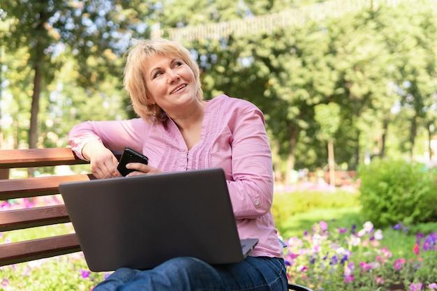 Una donna che lavora con un laptop su una panchina del parco. libero professionista donna di mezza età. studia email, social media.
