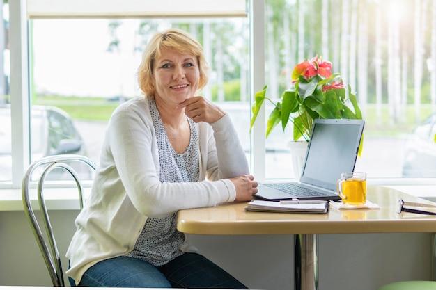 Una donna che lavora con un laptop a un tavolo vicino alla finestra in un bar, in ufficio. studia materiali per il lavoro.