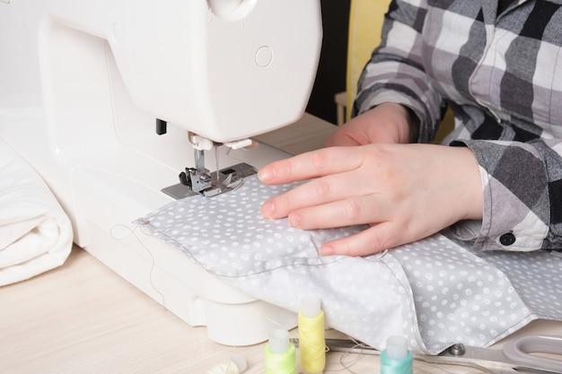Donna che lavora con la macchina da cucire, macchina da cucire bianca sul tavolo, processo di sartoria dei materiali per cucire
