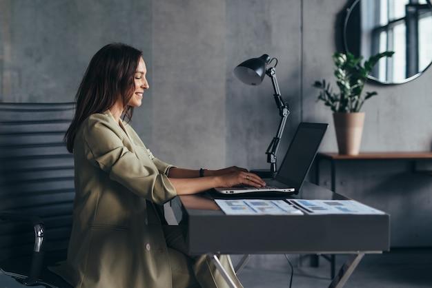 La donna lavora a casa seduta alla sua scrivania con il suo laptop.