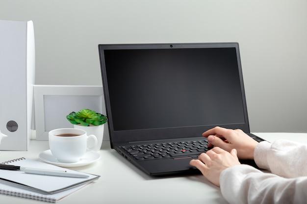 La donna lavora al computer portatile nell'istruzione online sull'area di lavoro. mani femminili che digitano sul computer portatile. display del computer portatile nero vuoto. posto di lavoro in home office per il lavoro a distanza in stile minimale sul muro bianco.