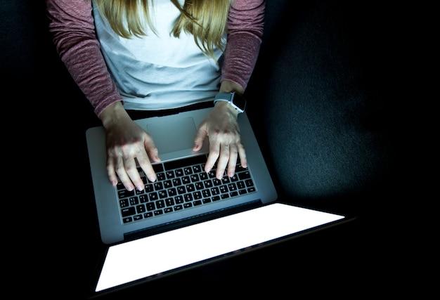 La donna lavora fino a tardi seduto sul divano con il computer portatile